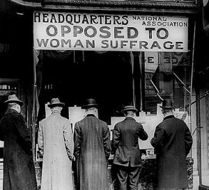 """An historical photograph of men  standing outside a doorway under a sign that read"""" Headquarters National Association Opposed to Woman Suffrage"""""""